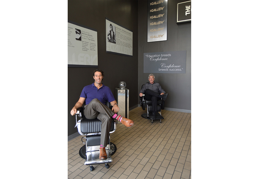 Two men smiling at the camera while sitting in black hydraulic salon styling chairs.