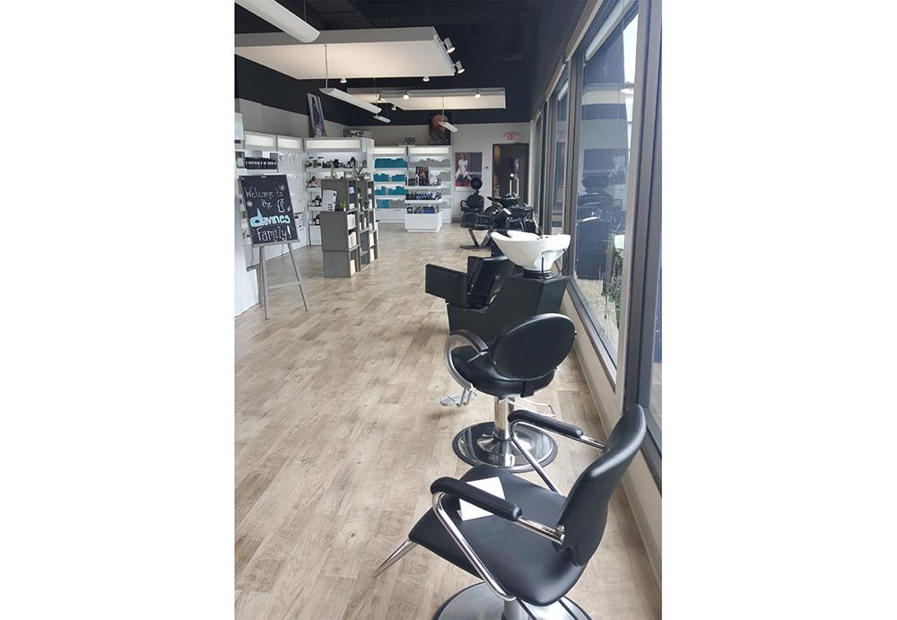 Classic black hydraulic salon styling chairs and shampoo chairs lined up along salon window.