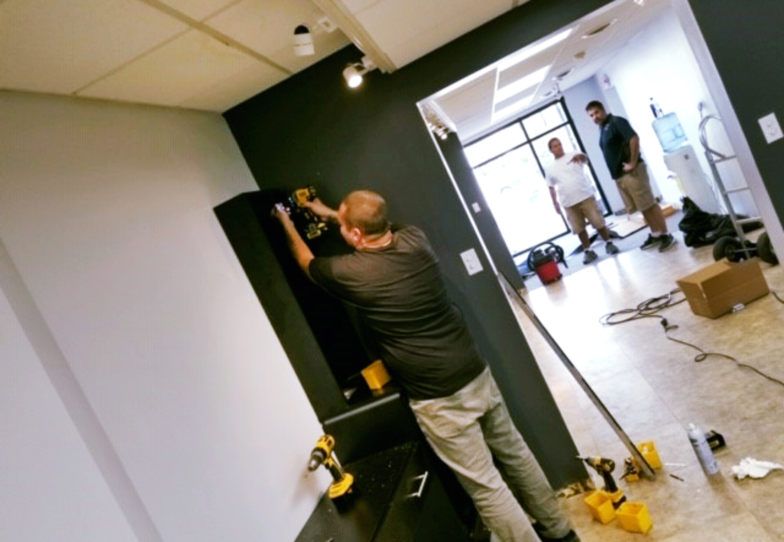 Man using a drill to install hair salon fixtures and design elements.