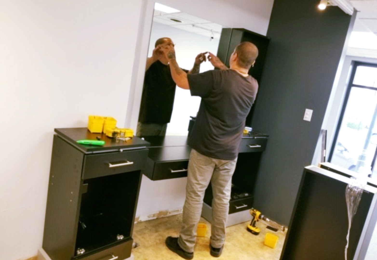 Man installing a mirror at a hair styling station in a salon under construction.