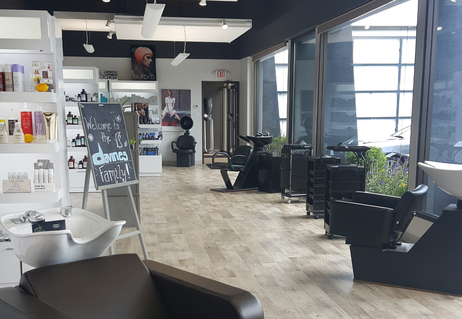 Hair salon with salon furniture along the windows including shampoo chairs and beauty salon trolley carts.