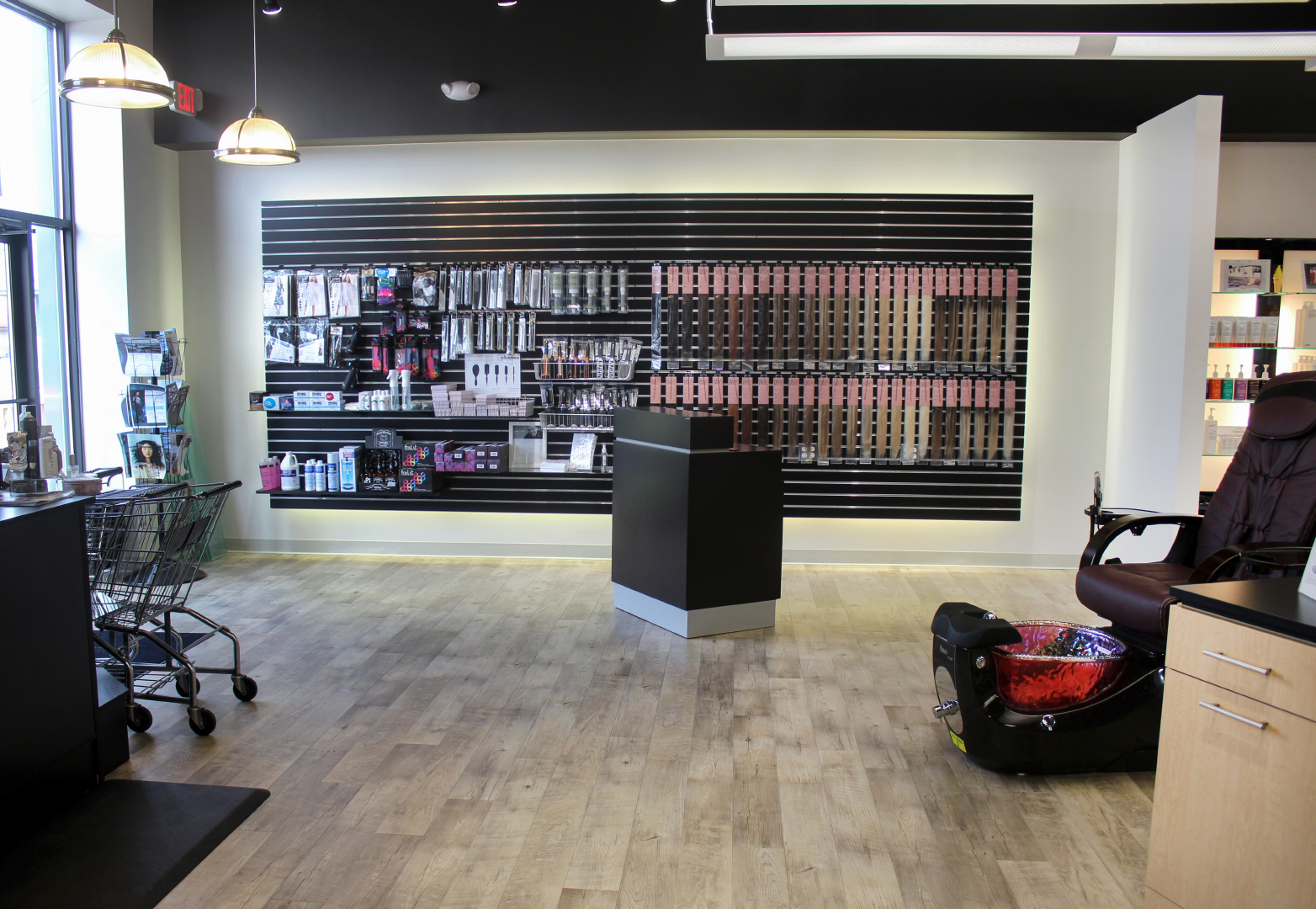 Hair salon displaying hair products along wall including hair extensions.