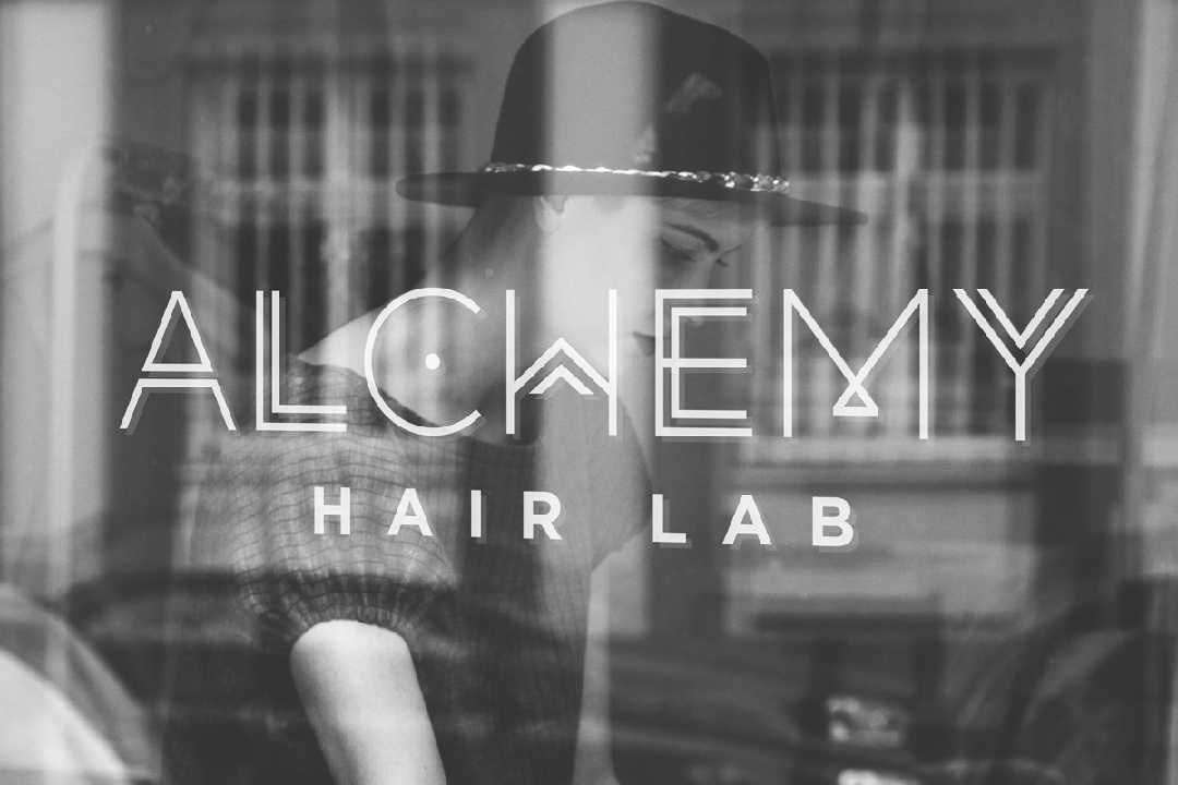Black and white photo of a hair salon logo design for Alchemy Hair Lab displayed on salon window.